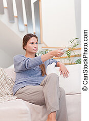 Portrait of a woman switching channel with a remote