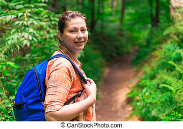 portrait of a woman with a backpack in a green forest in a hike