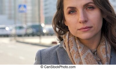 Portrait of a woman with a hairstyle and neutral makeup on a city background closeup