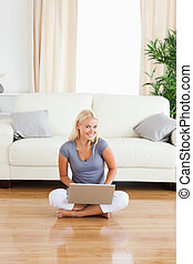 Portrait of a woman with a laptop while sitting on the floor