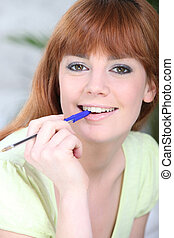 Portrait of a woman with a pen in her mouth