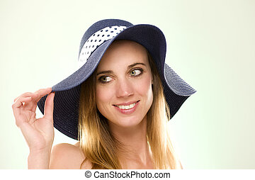 portrait of a woman with a summer hat on light green background