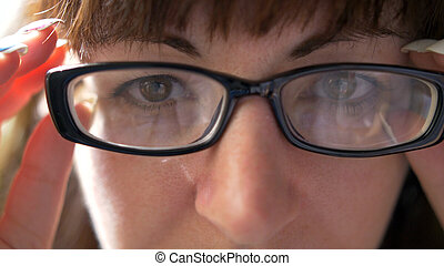 Portrait of a woman with glasses looking into the camera, close-up