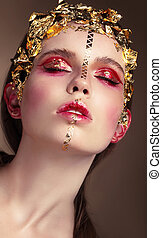 Portrait of a woman with gold makeup