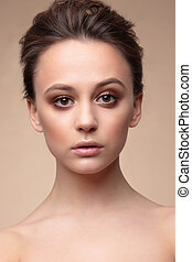Portrait of a woman with natural make-up. Beige color....