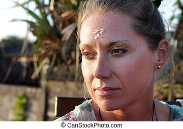 Portrait of a woman with rice on her forehead