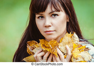 Portrait of a woman with yellow leaves in an autumn Park