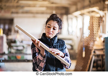 Portrait of a woman worker in the carpentry workshop, holding a wooden plank.
