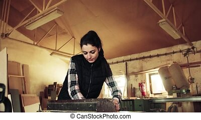 Portrait of a woman worker in the carpentry workshop, working with wood.