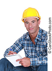 Portrait of a worker writing in notebook