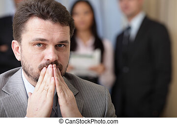 Portrait of a worried businessman with his team working behind