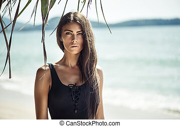 Portrait of a young, alluring woman on a beach