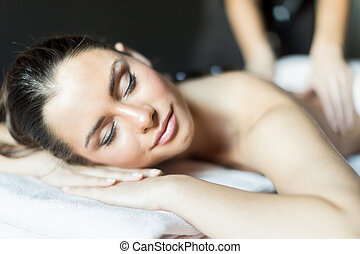Portrait of a young and beautiful woman being massaged with hot stones on her back
