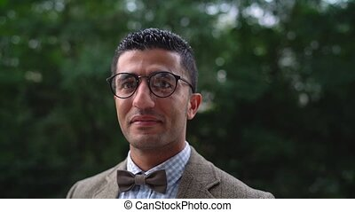 Portrait of a young Arab smiling man in glasses. Slow motion