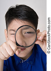 portrait of a young asian child looking through a magnifying...