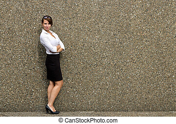 Portrait of a young attractive business woman against grey wall - copy space