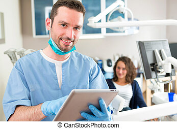 Portrait of a young attractive dentist in his office