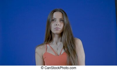 Portrait of a young attractive girl, with long hair on a blue background in the studio. Slow motion.