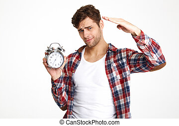 Portrait of a young attractive man holding alarm clock