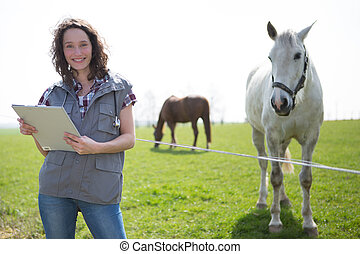Portrait of a young attractive veterinary in fields with...