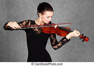 Portrait of a young attractive violinist woman in a black evening dress over grey background