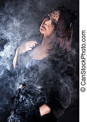Portrait of a young attractive woman in a puff of smoke