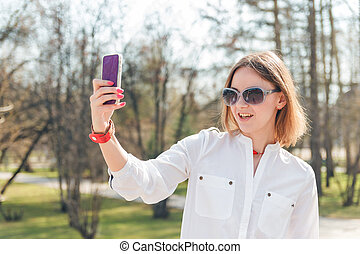 young attractive woman making selfie photo on smartphone