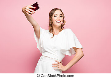 Portrait of a young attractive woman making selfie photo with smartphone on a pink background