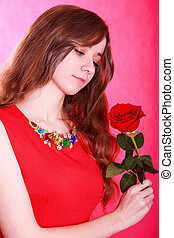 Portrait of a young attractive woman with a red rose