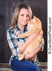 Portrait of a young attractive woman with cat in hands