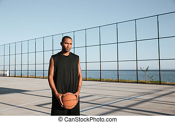 Portrait of a young basketball player standing at the playgroung