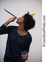black woman in party hat blowing in whistle