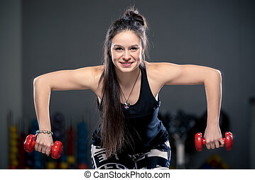portrait of a young beautiful brunette with dumbbells in the gym