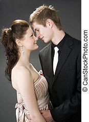Portrait of a young beautiful couple embracing. (gray background)