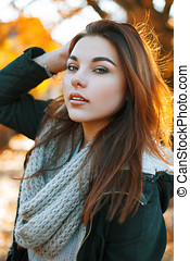 Portrait of a young beautiful girl in a knitted sweater on a sunny autumn day