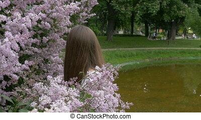 Portrait of a young beautiful girl in a lilac bush. Hair develops in the wind. Slow motion. Beauty and health. Healthy lifestyle.