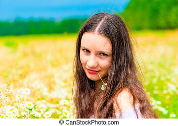 Portrait of a young beautiful girl in camomile field