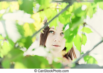 Portrait of a young beautiful girl in the foliage