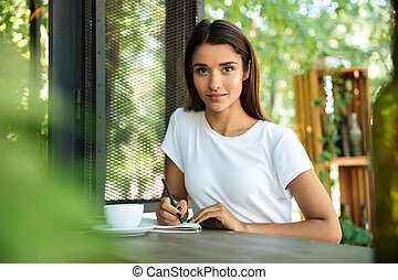 Portrait of a young beautiful girl making notes in a textbook