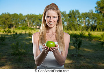 Portrait of a young beautiful girl with green apple outdoor