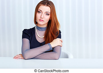 Portrait of a young beautiful pensive woman sitting at the table