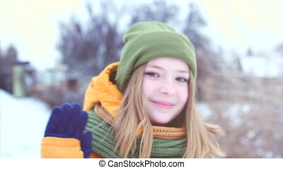 Portrait of a young beautiful teenage girl girl with blond hair blowing the wind, enjoying winter day outdoors, the girl with a green-brown scarf in a green hipster hat smiling happy looking into the camera close-up. Slow motion.