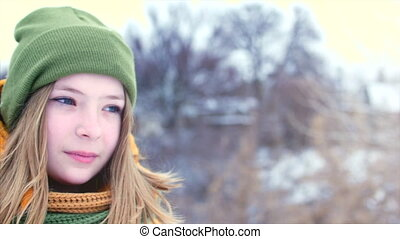 Portrait of a young beautiful teenage girl with blond hair, around the snow, girl with a green and brown scarf in a green hipster hat, smiling, looking around in different directions. Slow motion