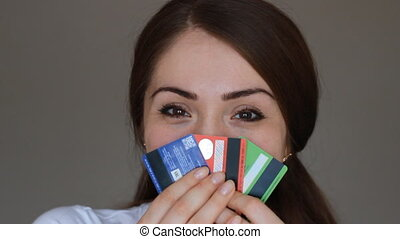 Portrait of a young beautiful woman close-up, who is smiling, looking at the camera and holding credit bank cards of different colors and banks. The concept of choosing and saving credit, finance, and economy.