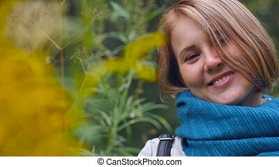 Portrait of a young beautiful woman enjoying autumn in the park