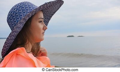 Young beautiful woman in a bright dress stands on the seashorePortrait of a young beautiful woman in a hat by the sea
