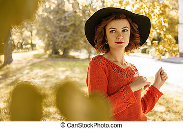 portrait of a young beautiful woman in a hat on a Sunny autumn day