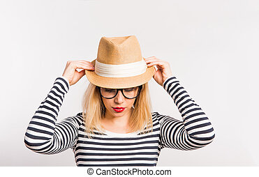 Portrait of a young beautiful woman in studio, holding a hat.