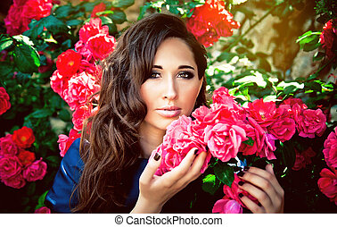 Portrait of a young beautiful woman in the flowering roses
