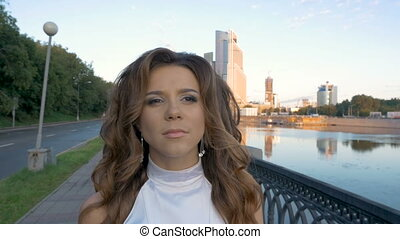 Portrait of a young beautiful woman. Which walks in the morning on the city embankment, along the river.